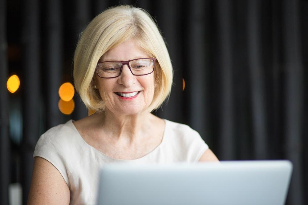 Closeup of Smiling Senior Woman Working on Laptop